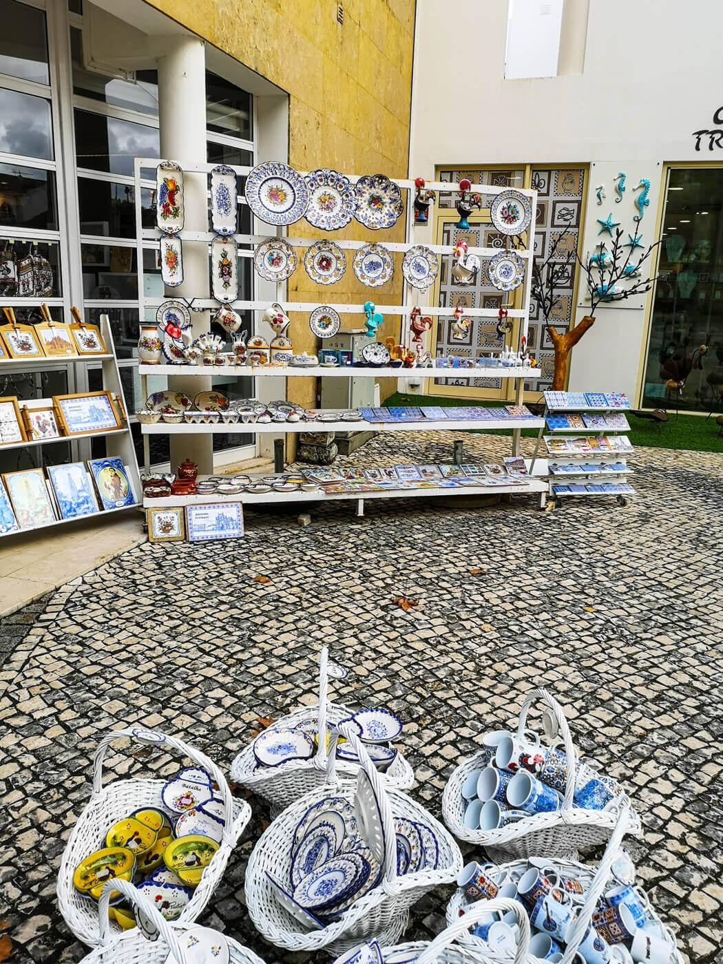A gift shop display full of china plates, mugs and tiles.