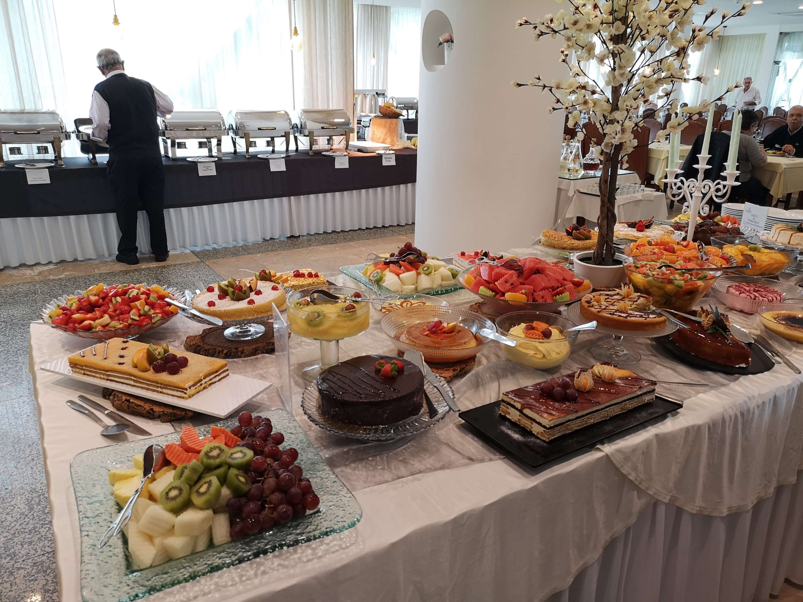 A large table full of various cakes and desserts.