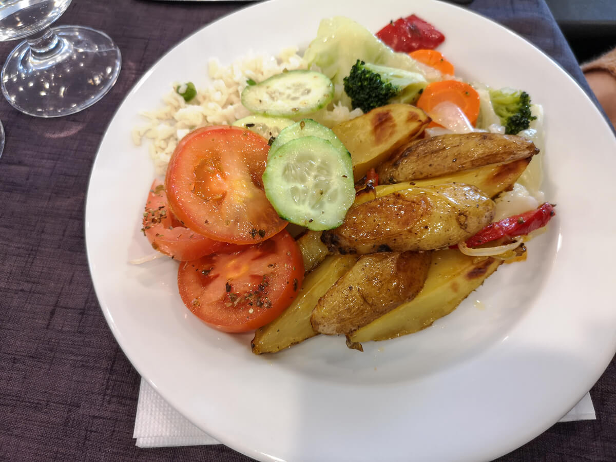 A plate of food including potato wedges, salad, broccoli and rice.