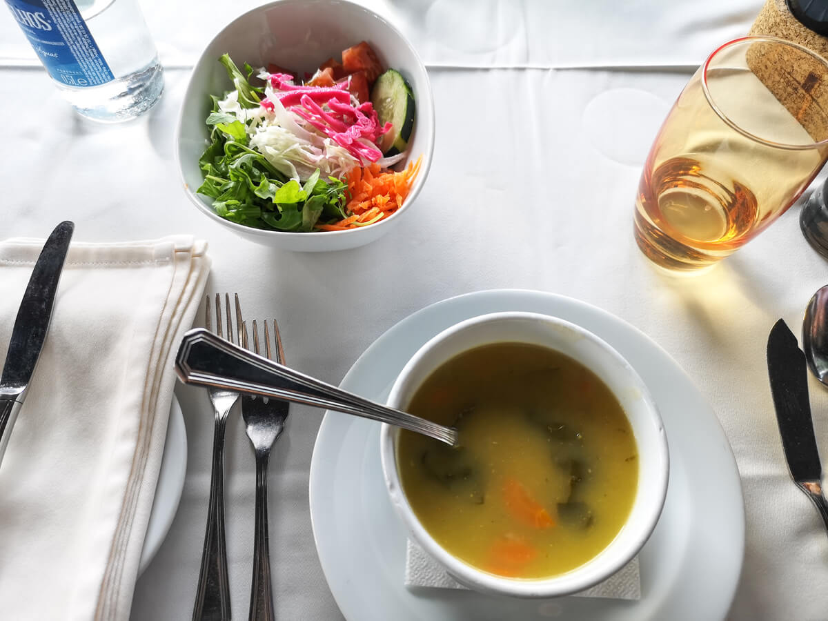 A bowl of vegetable soup and salad.