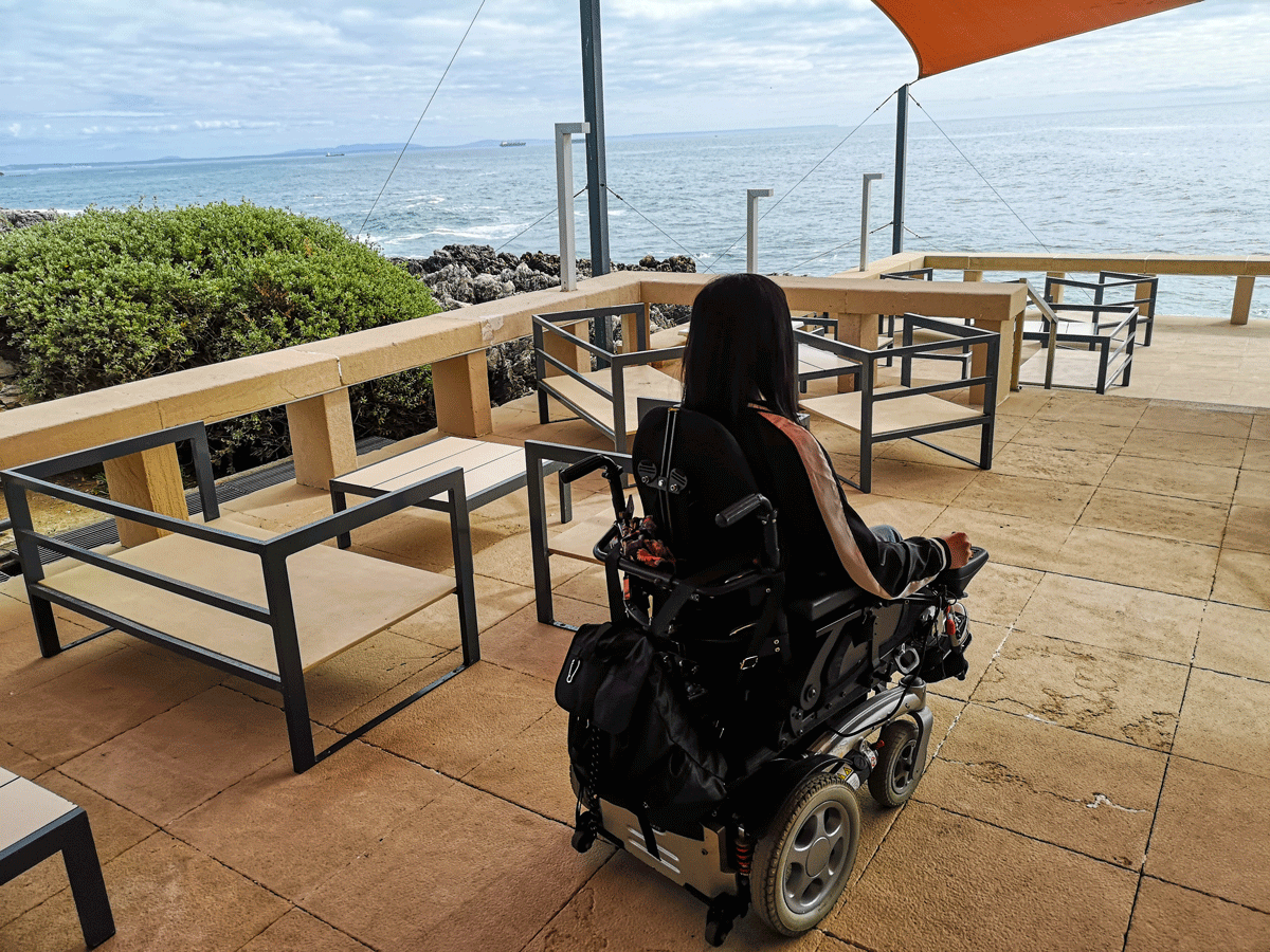 Emma sitting in her wheelchair with her back to the camera. Emma is looking out across the ocean.