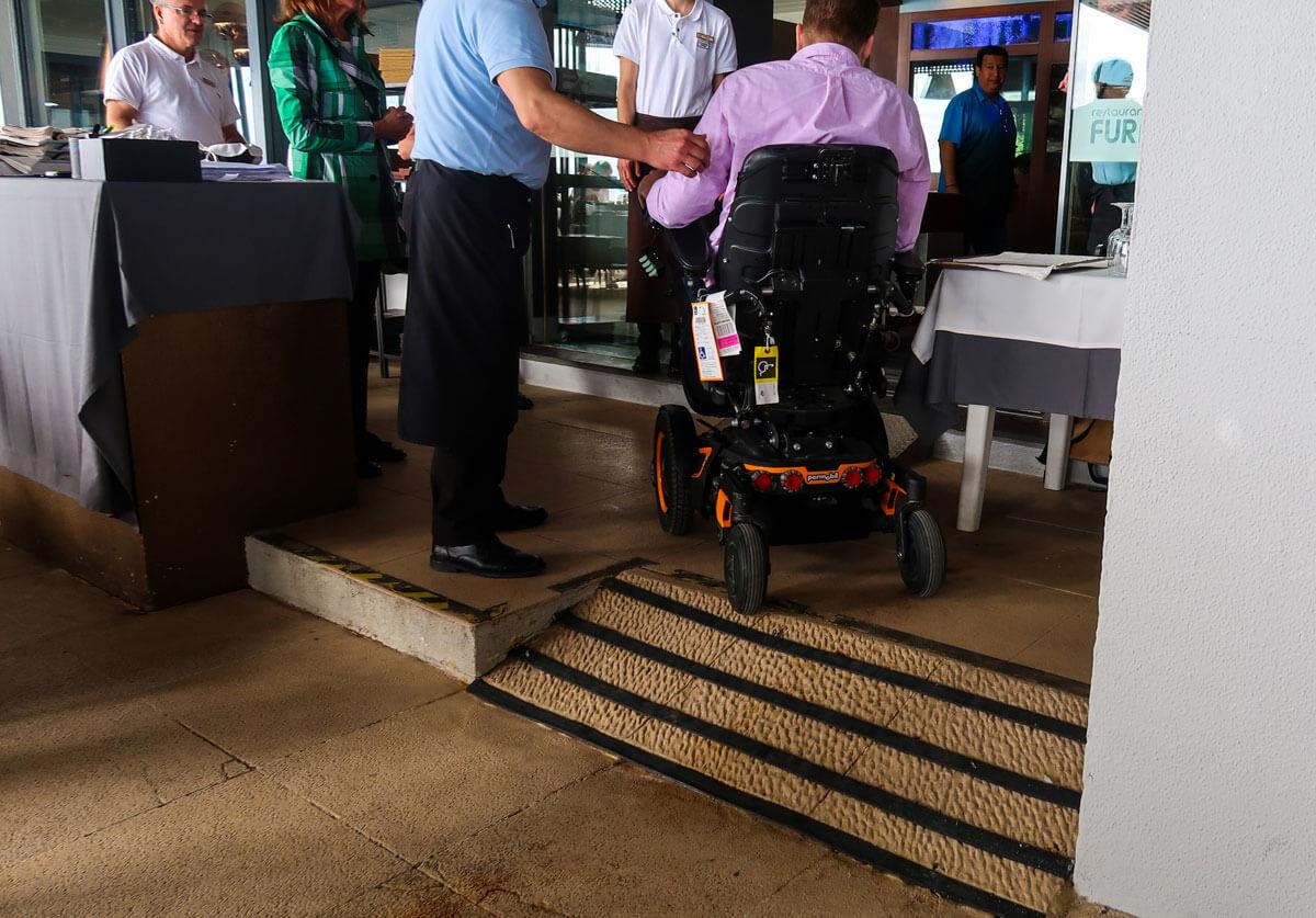 John, a power wheelchair user driving up a small ramp inside the restaurant.