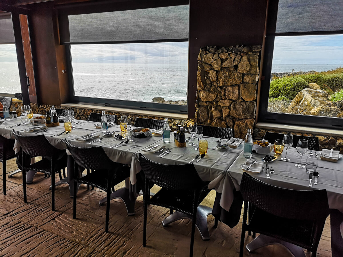 Dining tables positioned next to the windows with the view of the ocean.