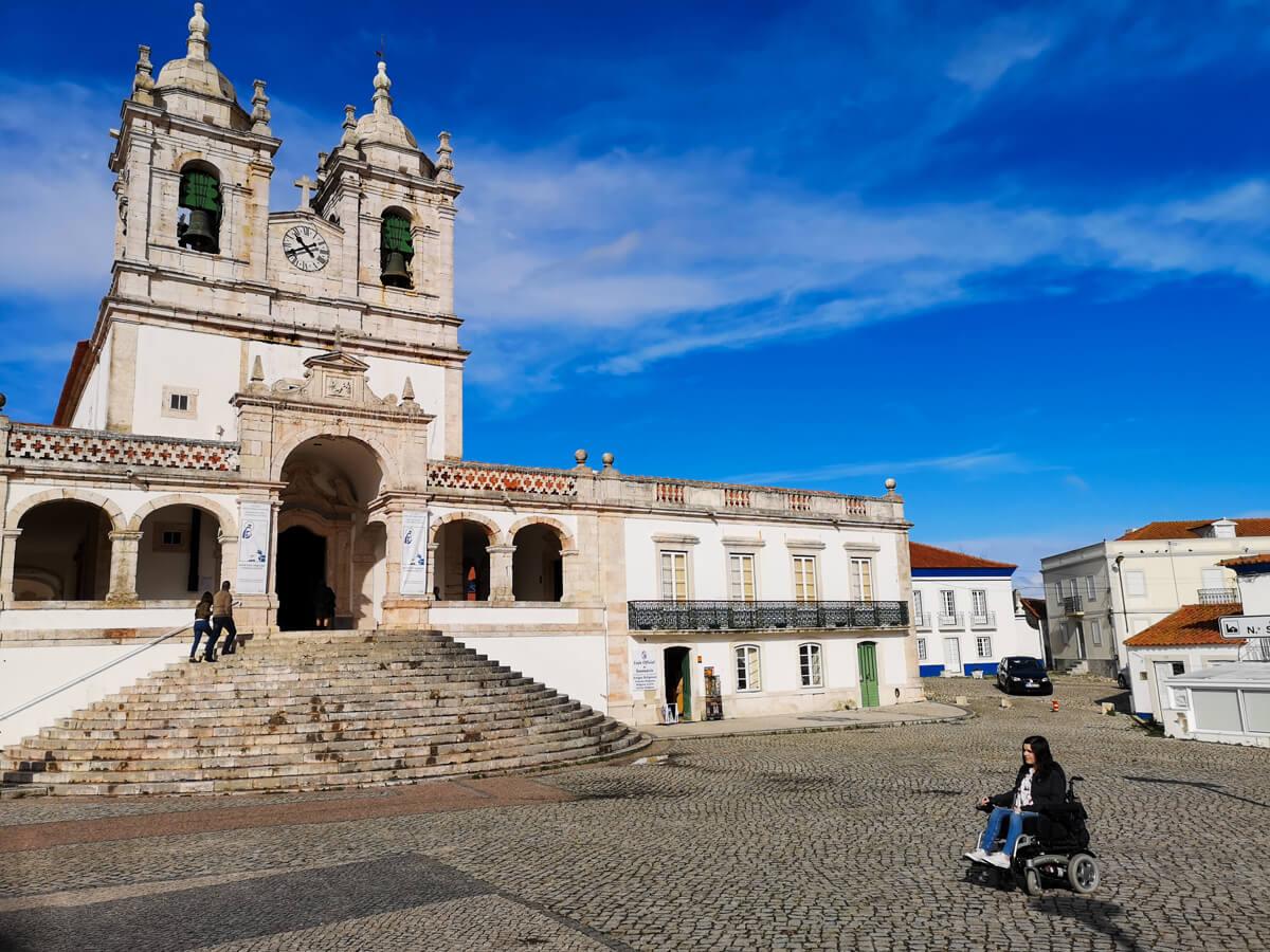 Emma driving along cobblestones in the village of Nazaré, Portugal.