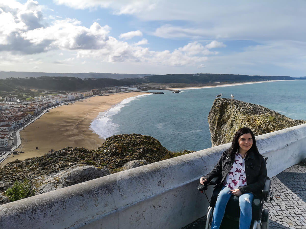 Emma sitting at the view point with the Nazaré beach behind her.