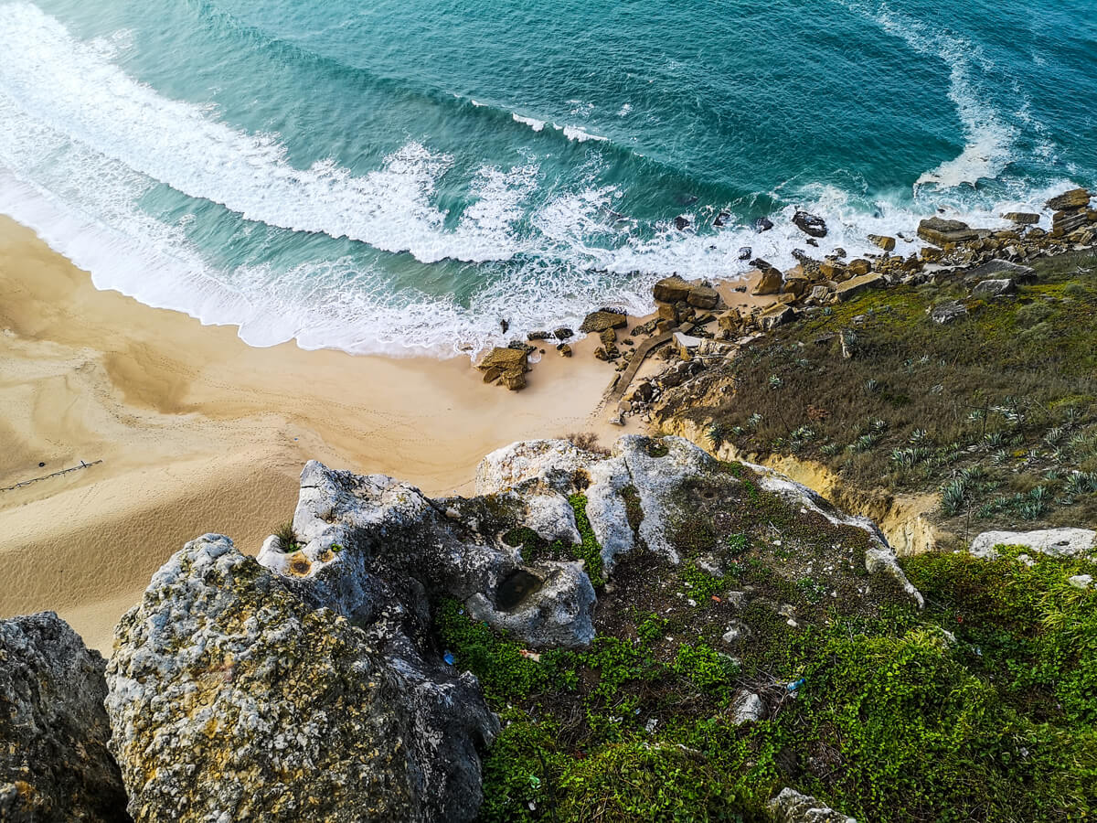 A view from above looking down at waves crashing against rocks. The water is turquoise green.