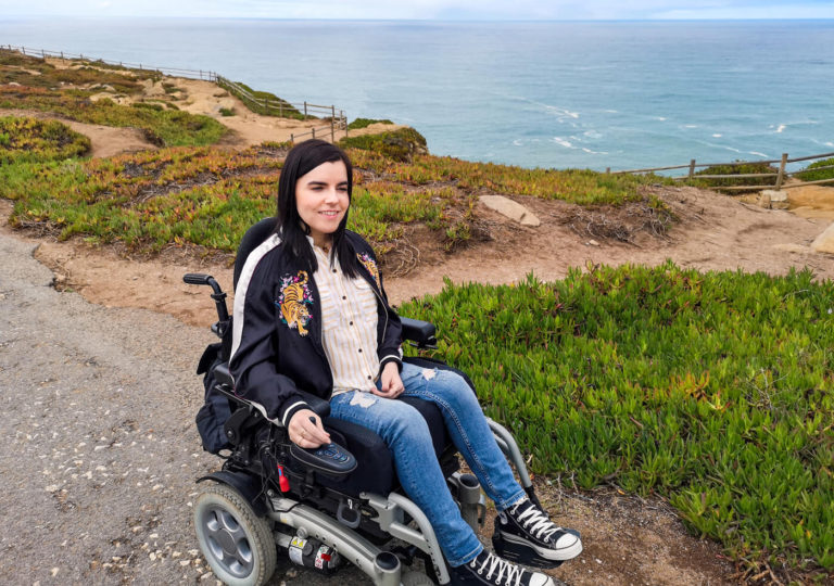 Emma sitting in her power wheelchair with the view of the ocean behind her at Cabo da Roca.