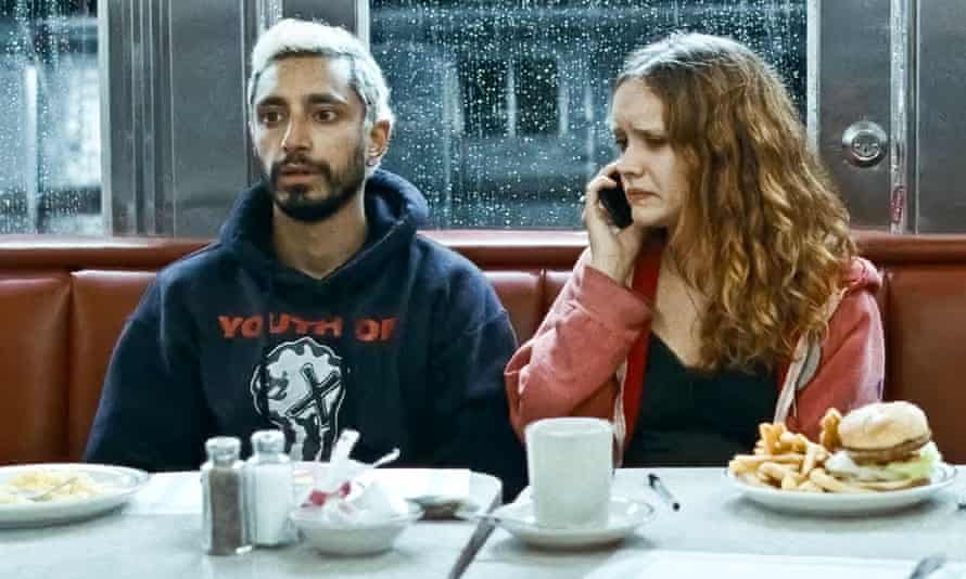 Riz Ahmed and Olivia Cooke in a screen from Sound of Metal. They are both sitting at a diner table with a plate of food in front of them.