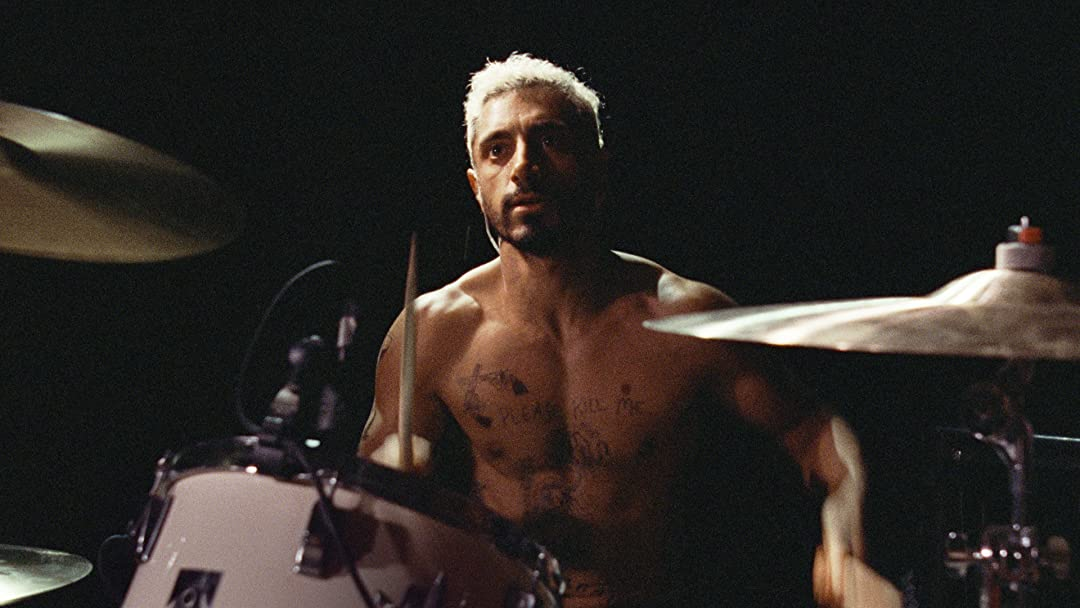 Riz Ahmed playing drums topless in a screen from Sound of Metal