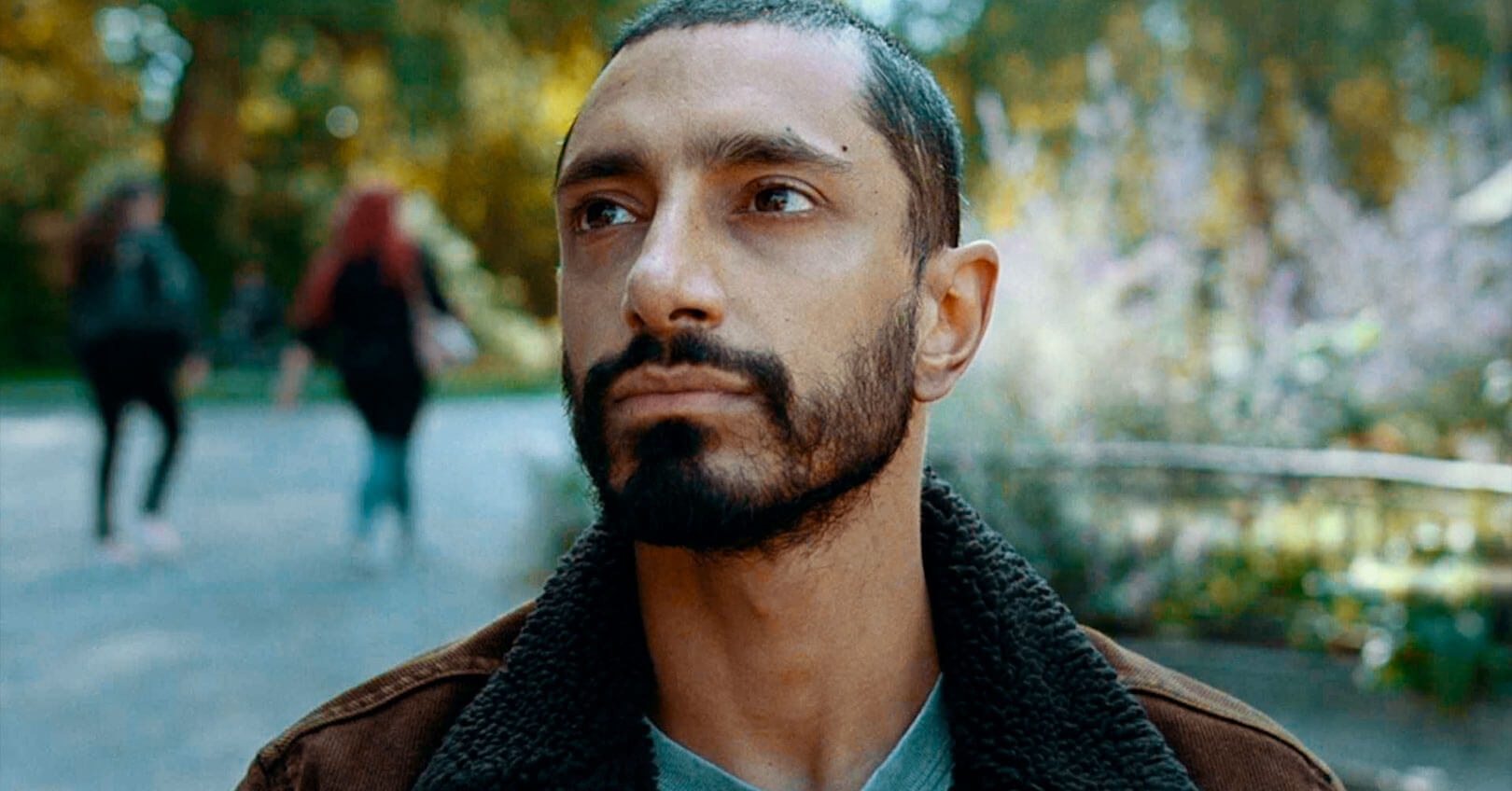 Riz Ahmed in a screen from Sound of Metal. He is sitting on a bench in Paris.
