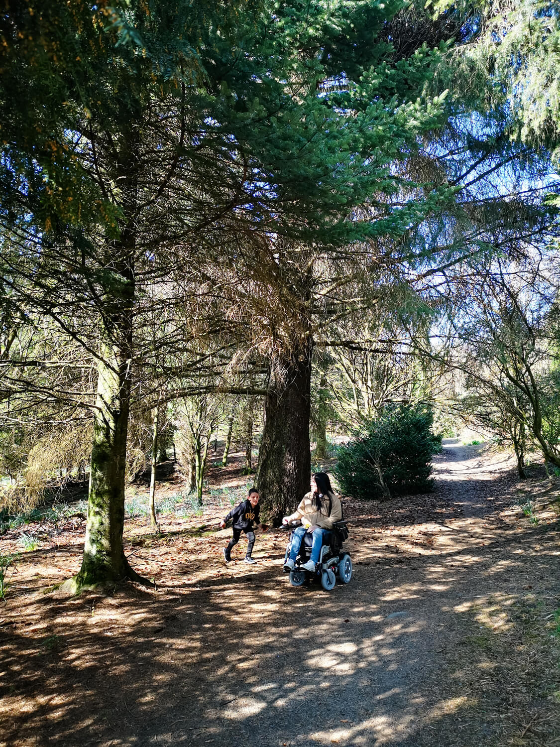 Emma driving her wheelchair through a forest nature trail with her nephew walking along beside her.