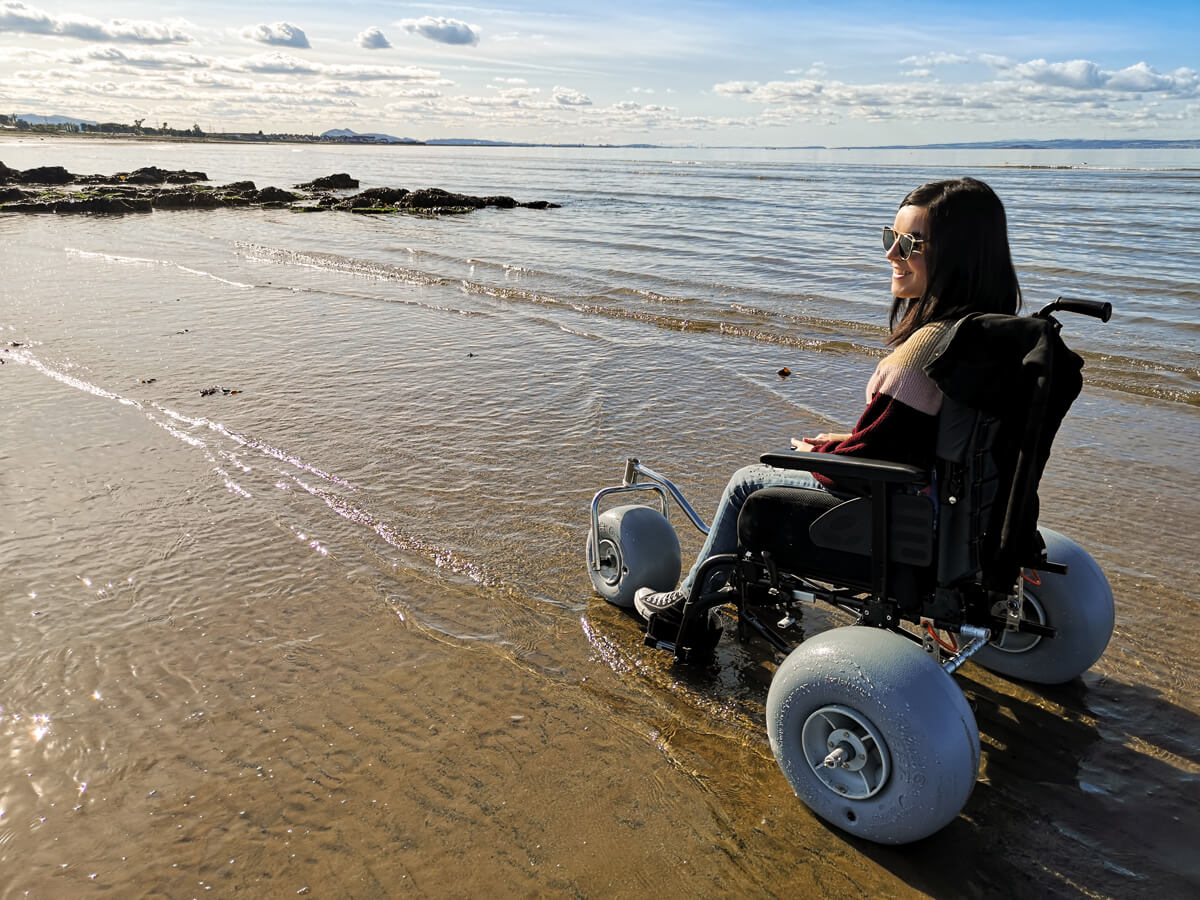 Emma sitting in a beach wheelchair on the beach at the edge of the water. Emma is looking out to the sea smiling.