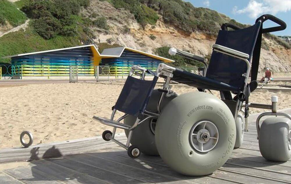 A beach wheelchair sitting on a wooden boardwalk with the beach and a colourful wheelchair accessible beach hut in the background