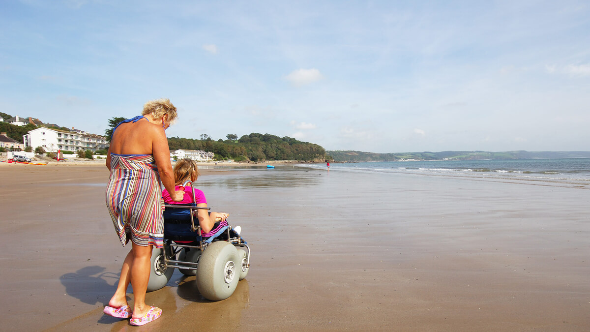A woman pushing another woman along the beach in a beach wheelchair at Broad Haven South beach, Pembrokeshire.