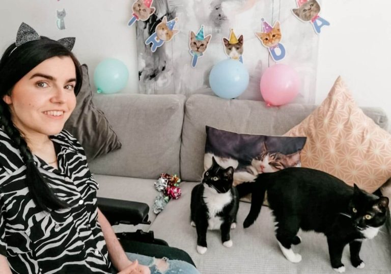 Emma sitting in her wheelchair in her livingroom wearing a black and white blouse and black cat ears. Her two black and white cats are sitting next to her on the sofa. Birthday banners are hanging on the wall behind them with cat faces on them and balloons.