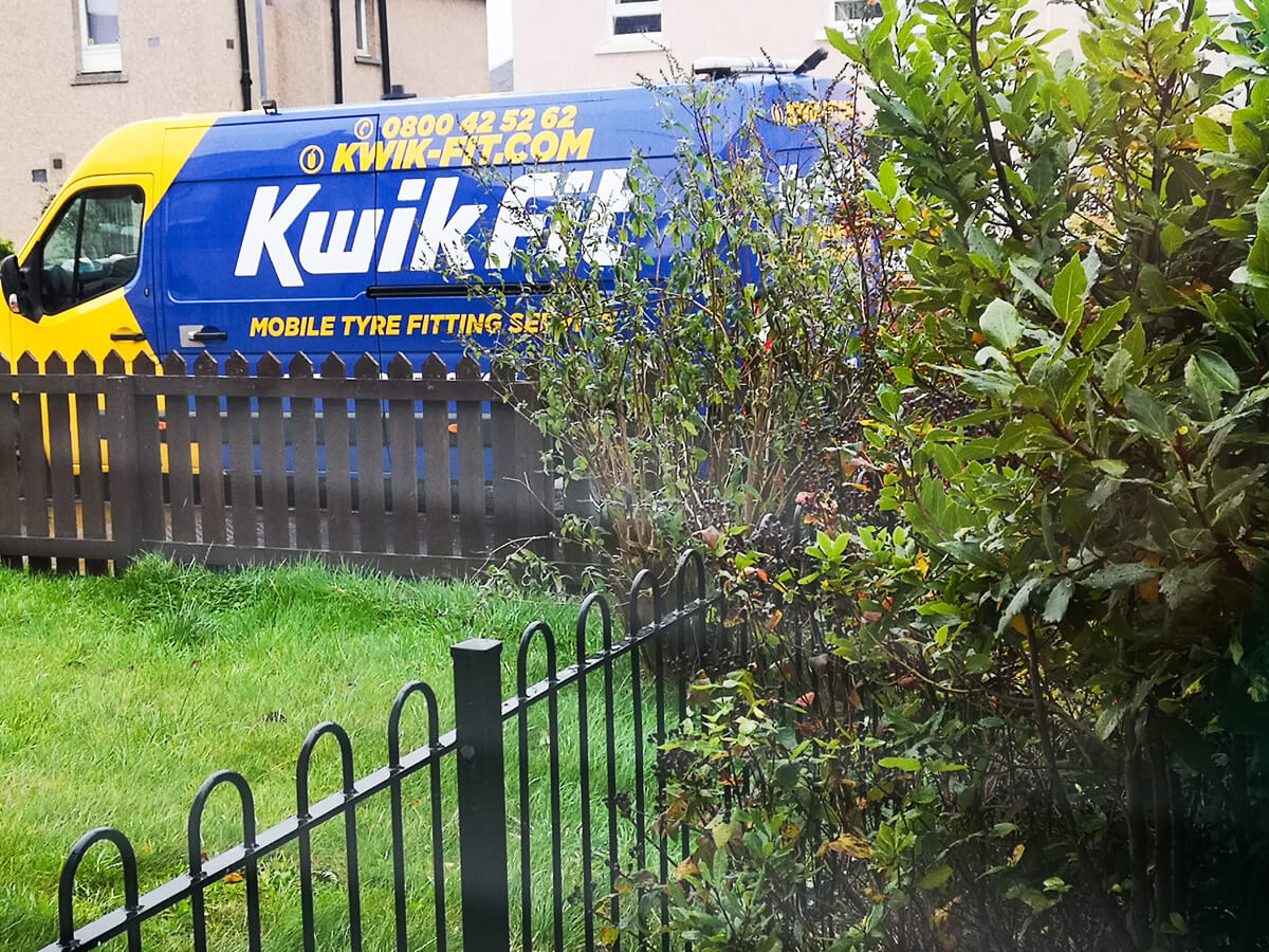 A blue and yellow Kiwk Fit van parked in a residential street. Bushes and grass are in view at the bottom of the photo.