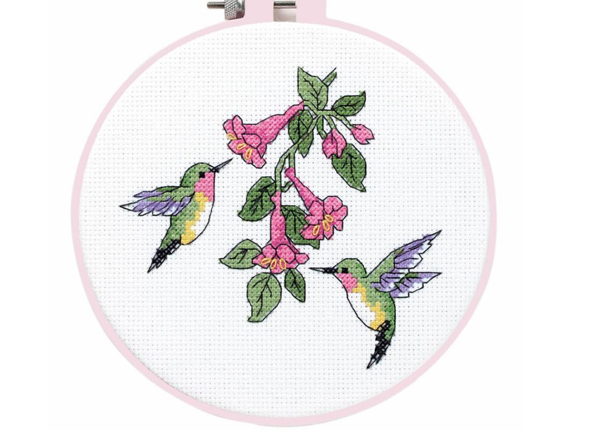 A cross stitch embroidery hoop with two hummingbirds and flowers.