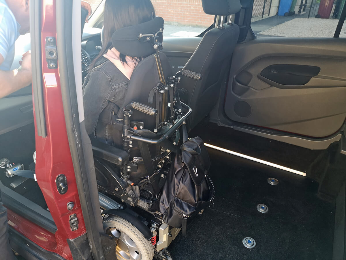Emma sitting upfront in the WAV in her powered wheelchair. There is space between her showing available storage space in the Ford upfront WAV.