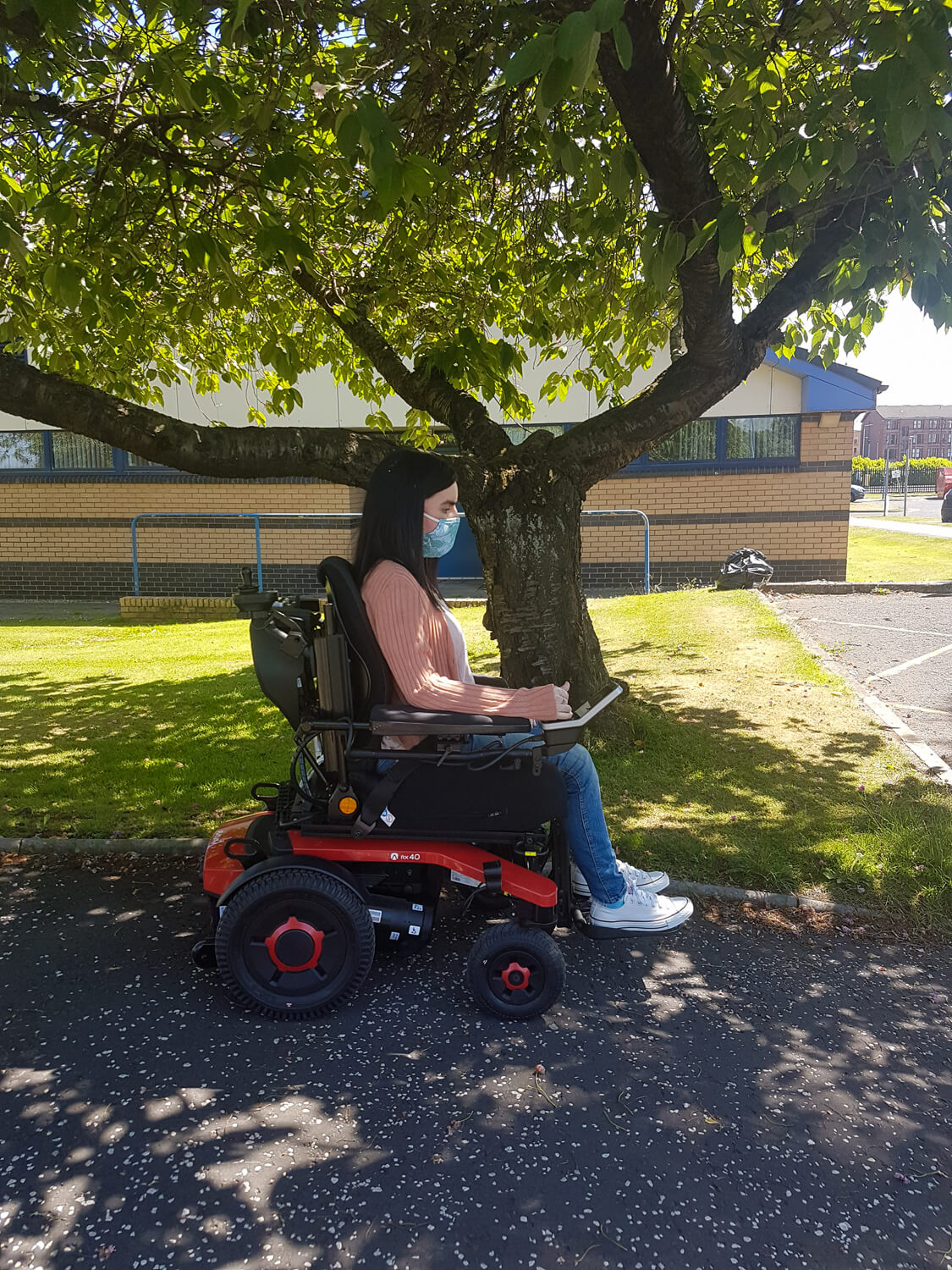 Emma, a white woman sitting in her powered wheelchair outside next to a grassy area and tree. Emma is wearing a peach cardigan, skinny jeans and white converse shoes. She has a face mask covering her nose and mouth.