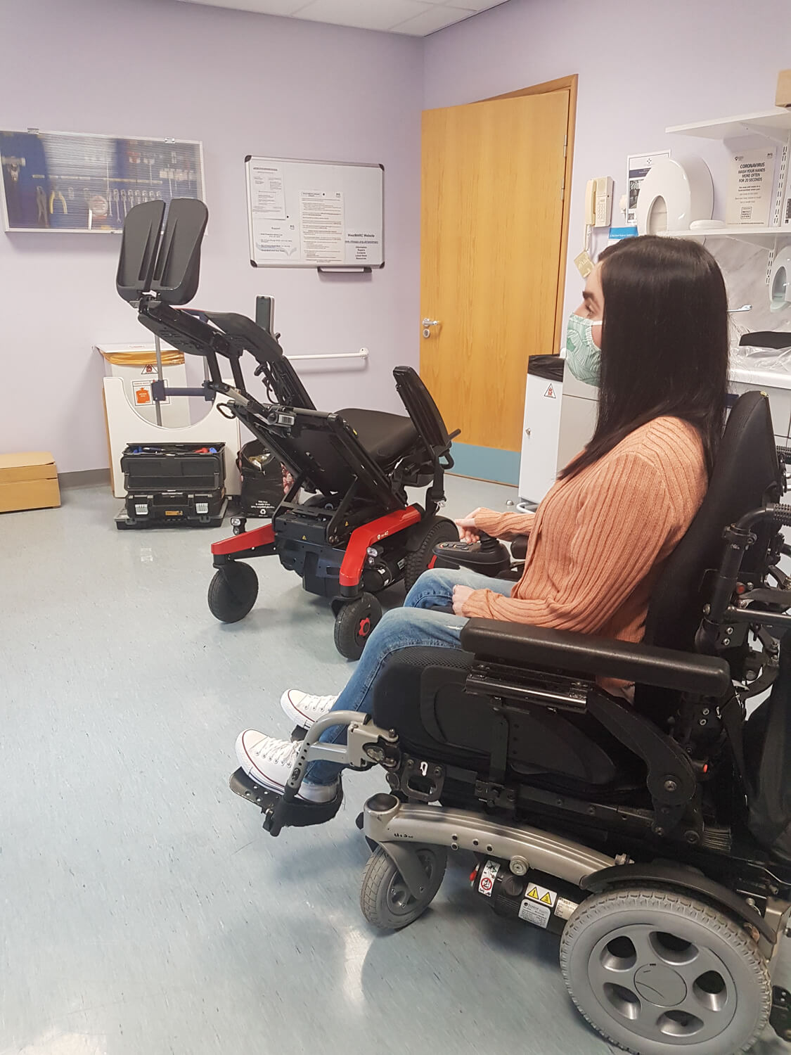 Emma, a white woman sitting in her powered wheelchair in a hospital consultation room. Emma is wearing a peach cardigan, skinny jeans and white converse shoes. Beside her is a black and red powered wheelchair which is reclined back with the footplates up.