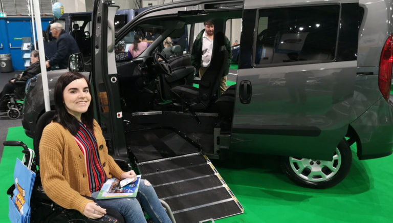 Emma, a white woman is sitting in her powered wheelchair next to a Infront Doblo wheelchair accessible vehicle (WAV). Emma is smiling at the camera and wearing blue skinny jeans, a camel coloured cardigan and stripey shirt.