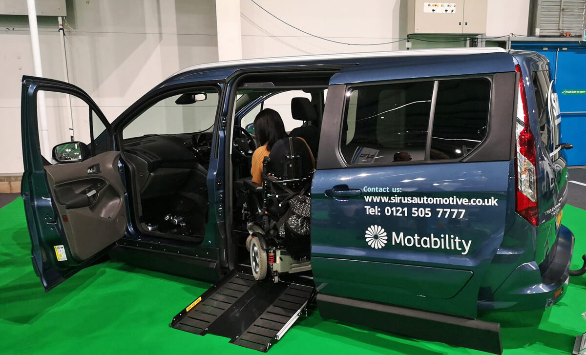Emma, a white woman is shown from the back driving her powered wheelchair into the Ford Sit upfront wheelchair accessible vehicle via the side entry ramp. The contact details for Sirus at displayed on the blue vehicle. The vehicle is sat on a bright green carpet at the One Big Day Motability Event.