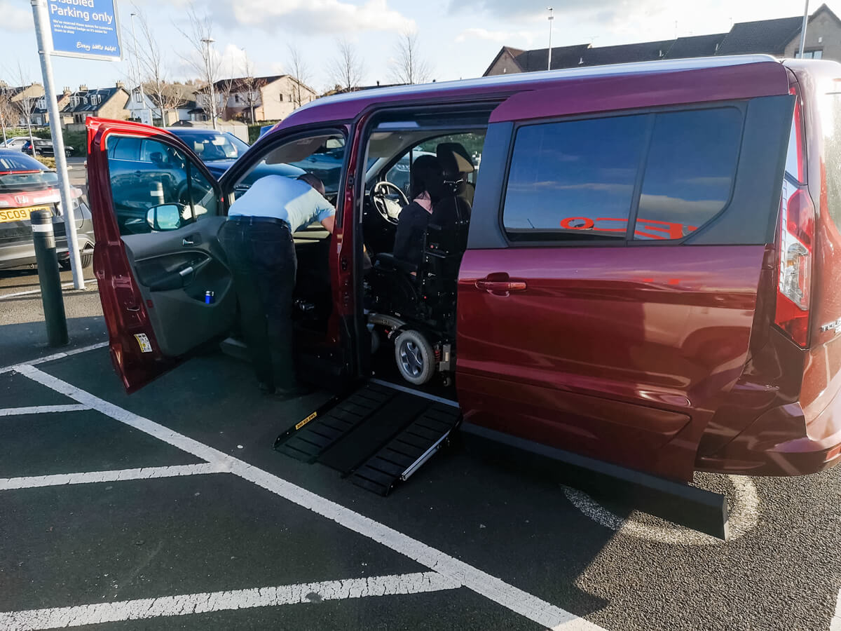 Emma sitting in her powered wheelchair in the front of the red vehicle while parked in a supermarket disabled parking bay. The male vehicle rep is leaning over in the front passenger door.