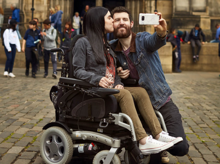 Emma in her powered wheelchair with her boyfriend kneeling beside her holding a phone up while taking a selfie of them together. Emma is giving him a kiss on the cheek. They are outside a Cathedral in Edinburgh.
