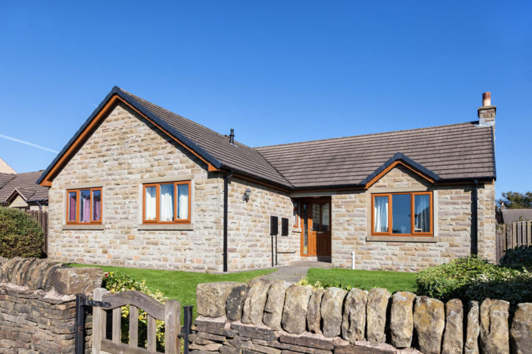 traditional stone bungalow with brown wooden windows and drystone wall at the front