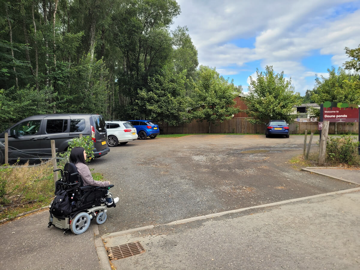 """Emma sitting in her power wheelchair. She is driving into a car park with four vehicles parked up. A sign on the right reads """"Welcome to Doune Ponds"""". The car park is surrounded by trees."""