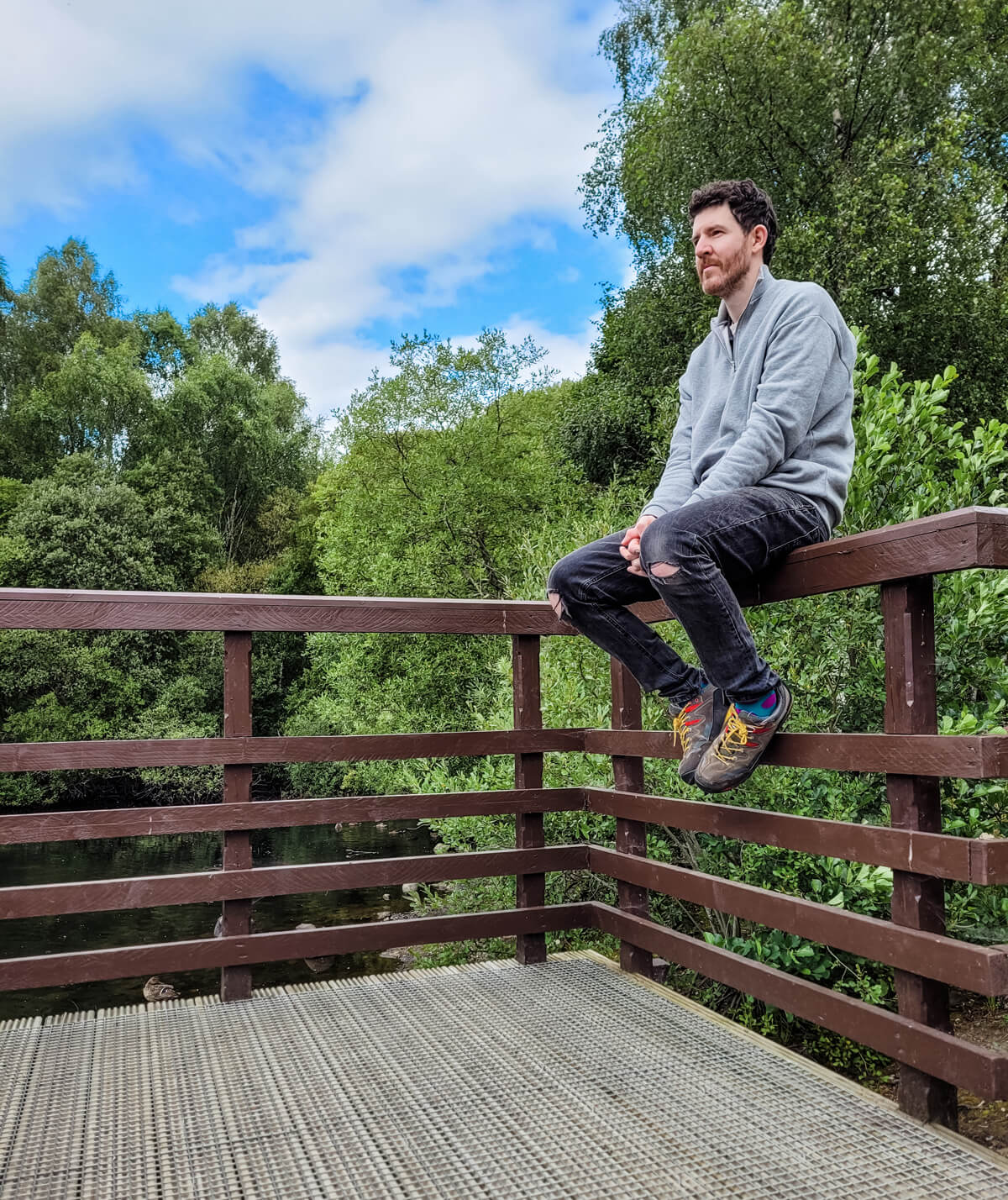 Allan sitting on the wooden deck looking out to the pond. Behind him are lush green trees and a blue sky.