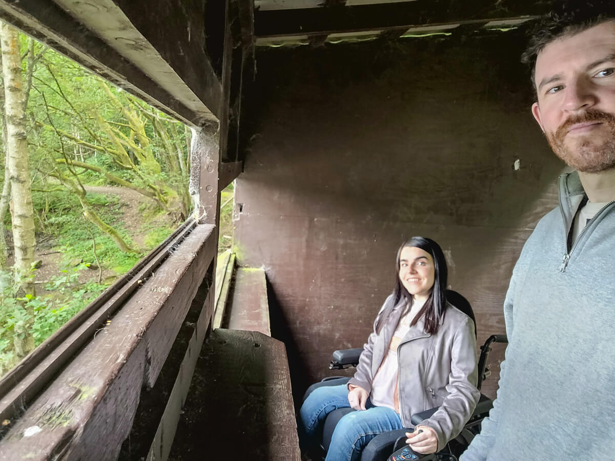 A selfie of Emma and Allan inside a bird hide. They are both smiling.