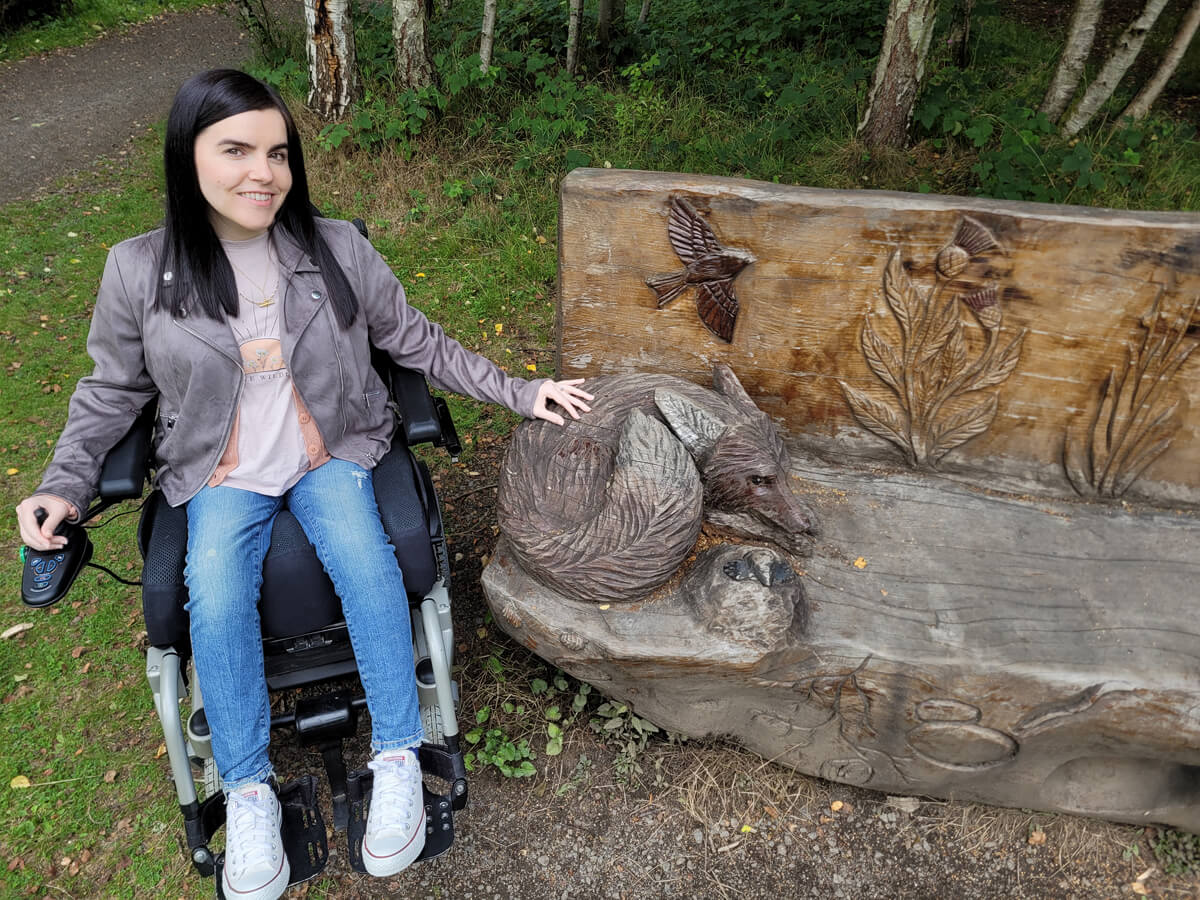 Emma sitting in her power wheelchair. She is looking up at the camera and smiling. She has her left hand on a wooden carving of a fox on a wooden bench.