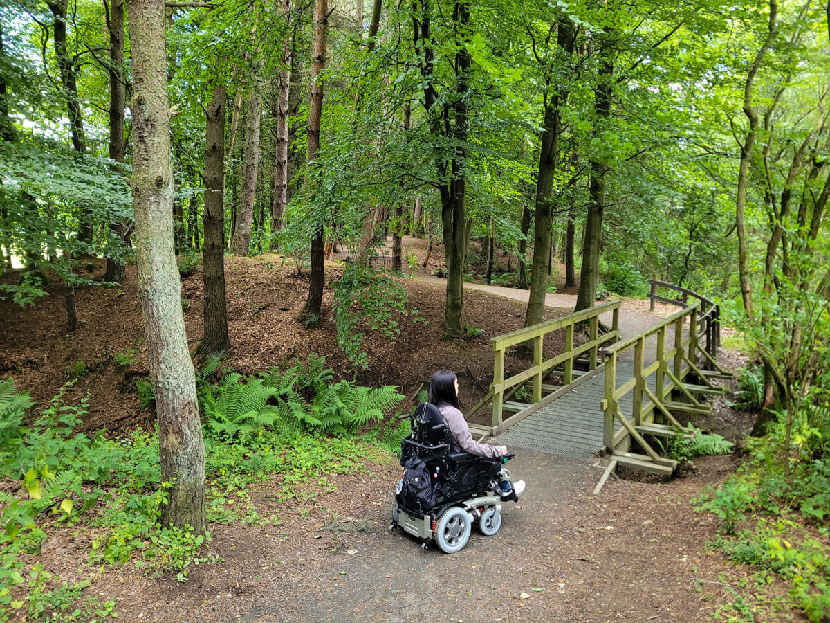 Emma in her powered wheelchair. She is driving across a wooden bridge in the forest. She is surrounded by lush green trees.