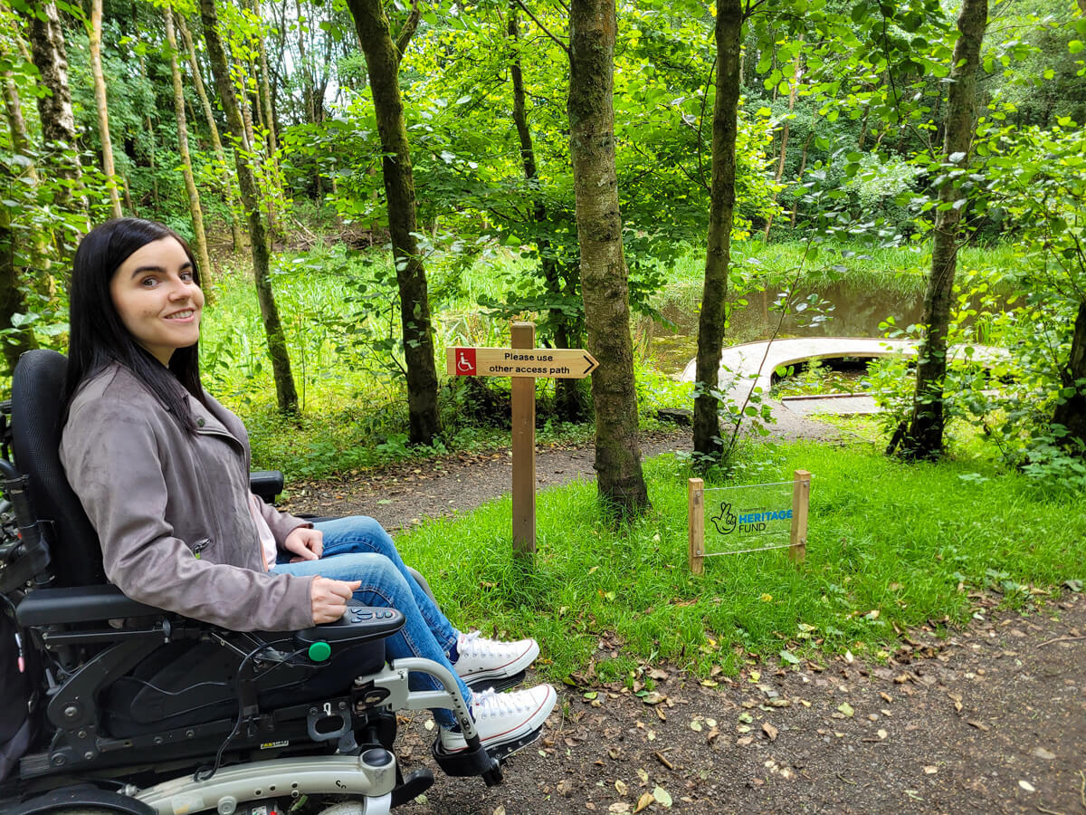 """Emma sitting in her wheelchair. She is on a raised platform above the pond. She is next to a sign which reads """"Please use other access path"""".nd."""