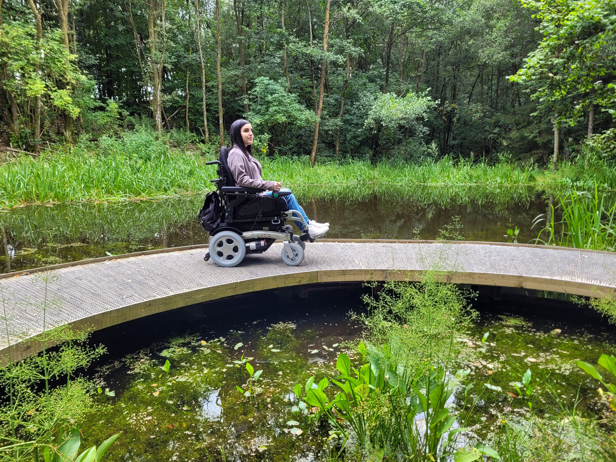 Emma sitting in her wheelchair. She is on a raised platform above the pond. She is looking off to the side. There are trees surrounding the pond.