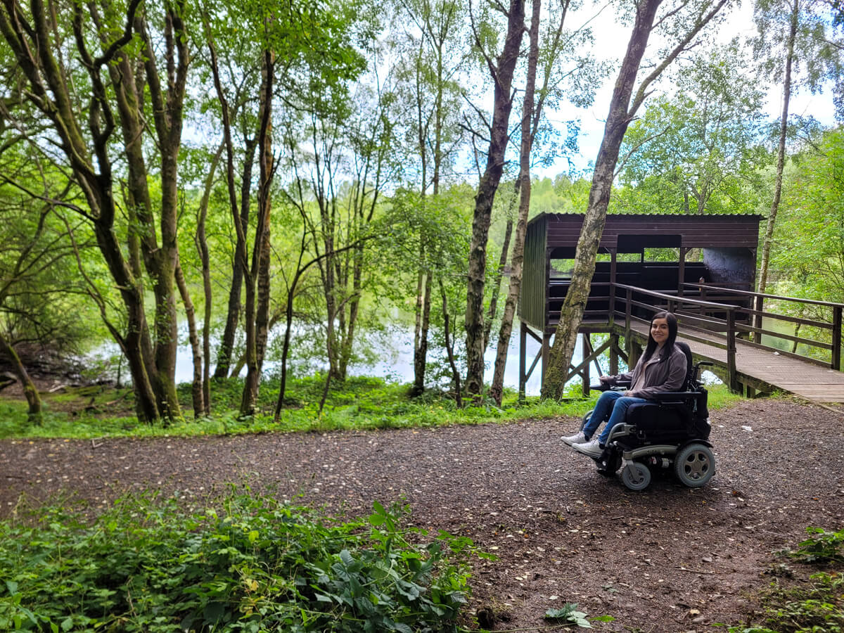 Emma driving along the wheelchair accessible trail at Doune Ponds. A bird lookout hide is behind her. Trees line the path.