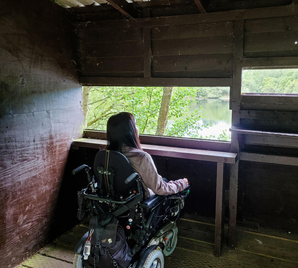 Emma sitting inside the bird lookout hide. She is looking out across the pond. Emma has her back to the camera.