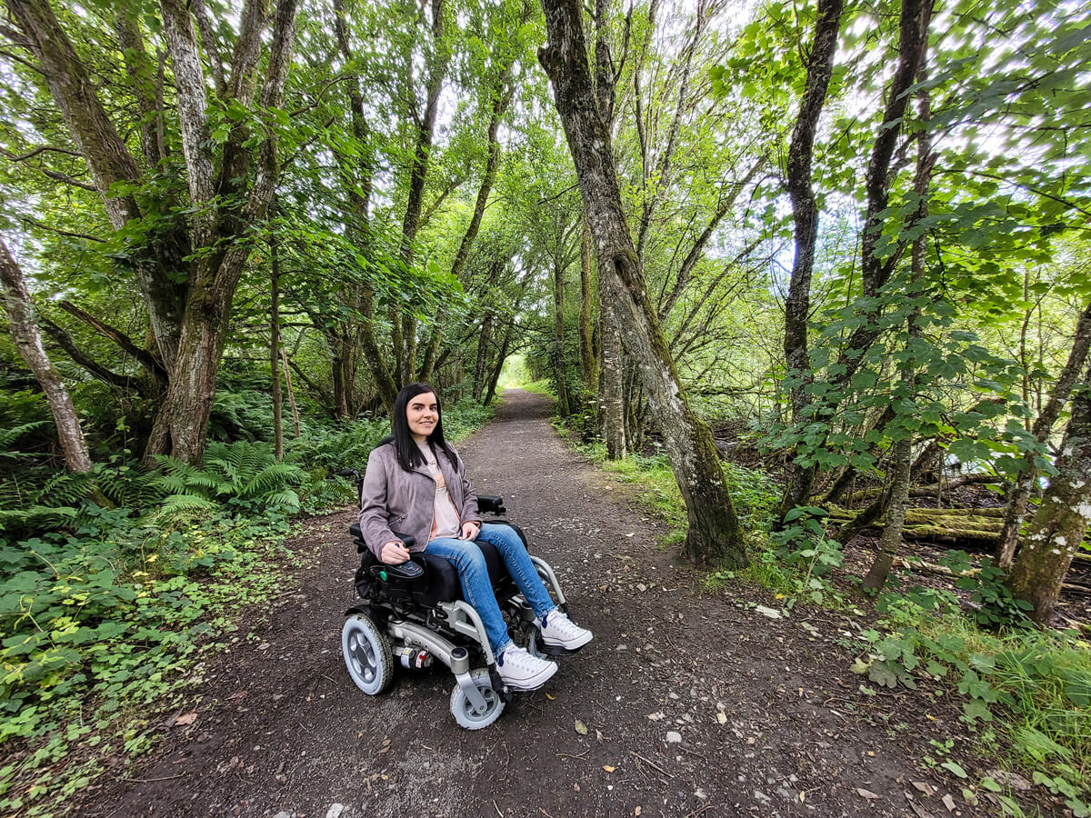 Emma on the wheelchair accessible trail through Doune Ponds. The path is lined with trees on each side.