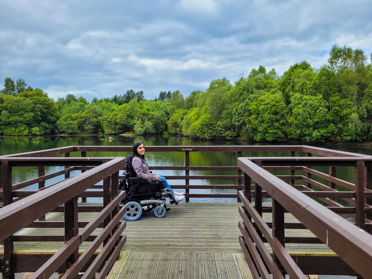 Emma sitting on the raised platform above the large pond. The pond is surrounded by trees.