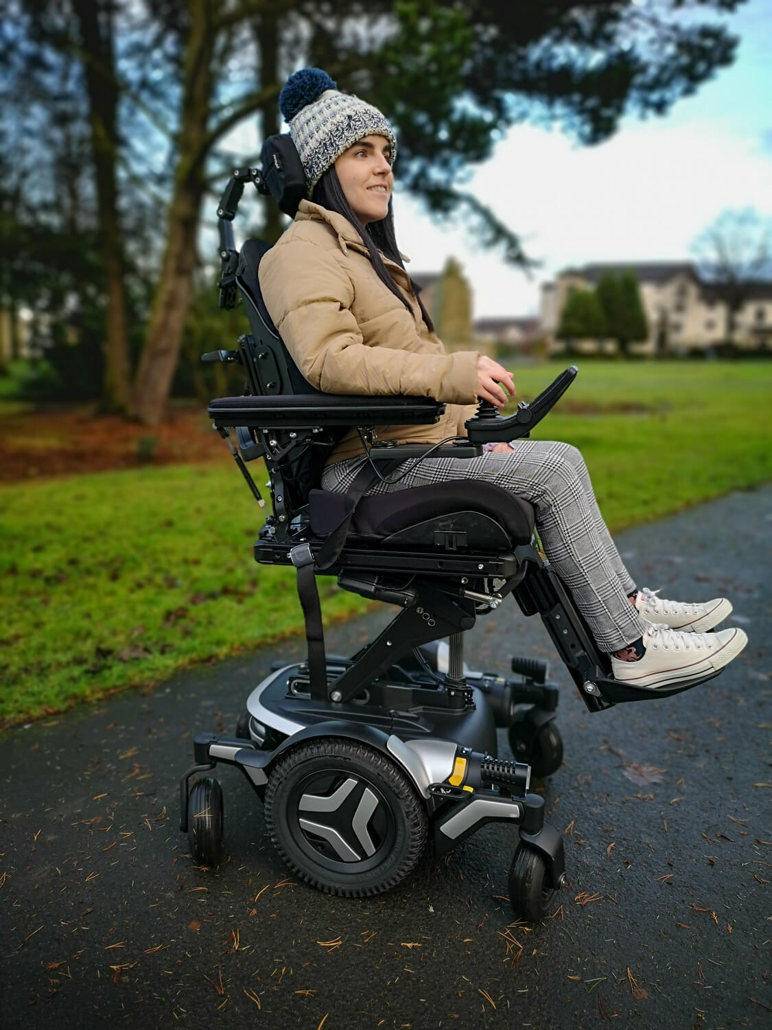 Emma, a wheelchair user sitting in a black and silver Permobil M3 wheelchair in a park. She is wearing a woolly hat, puffy jacket, black and white check trousers and white converse shoes. The wheelchair seat is elevated. Emma is smiling.