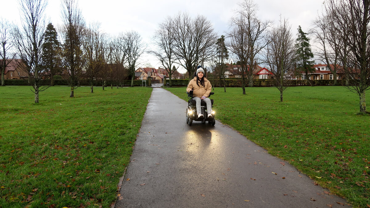 Emma driving her Permobil powerchair in the park. The wheelchair LED lights are turned on. Emma is wearing a woolly hat, puffy jacket, black and white check trousers and white converse shoes. Emma is smiling.