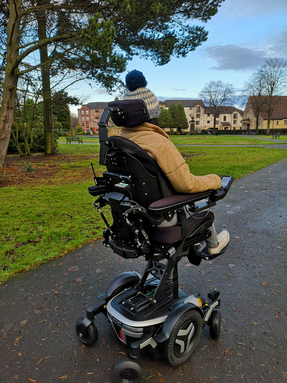 Emma, a wheelchair user sitting in a black and silver Permobil M3 wheelchair in a park. She is wearing a woolly hat, puffy jacket, black and white check trousers and white converse shoes. The wheelchair seat is elevated. Emma has her back towards the camera showing the back of the wheelchair. Trees and houses are in the background.
