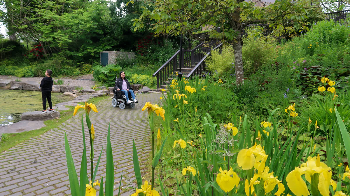 Emma and her nephew in the Riverside Park Heather Garden. They are next to a small pond surrounded by colourful plants.