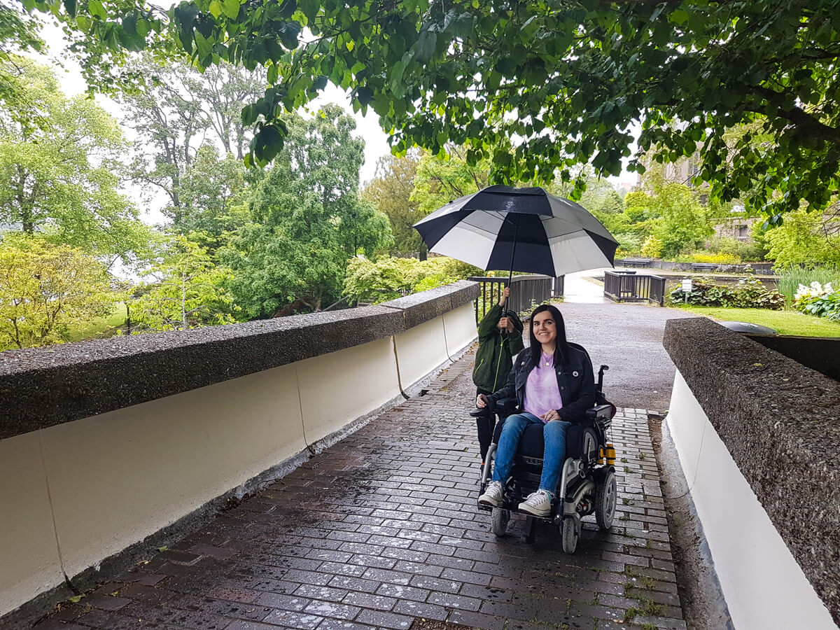 Emma, a powered wheelchair user is smiling at the camera while her young nephew holds a large umbrella over both of them.