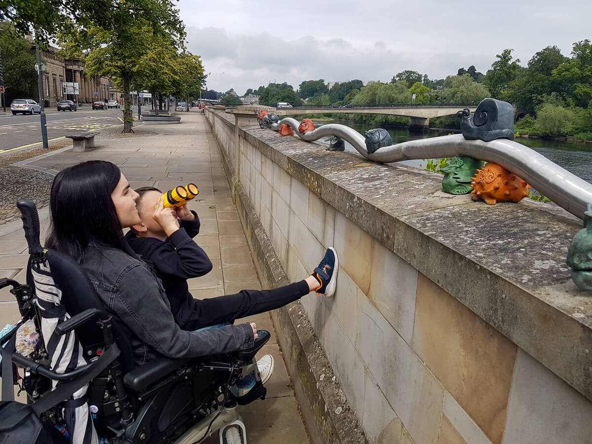 Emma sitting in her wheelchair. Her young nephew is sitting on her lap. He has yellow and black binoculars held up at his face. They are looking at the view across the river Tay. There are some small animal sculptures on the bridge beside them.