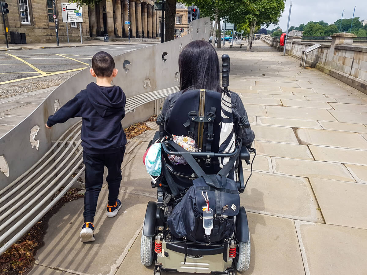 Emma driving her wheelchair along the street in Perth. Her nephew is walking beside her. Their backs are to the camera.