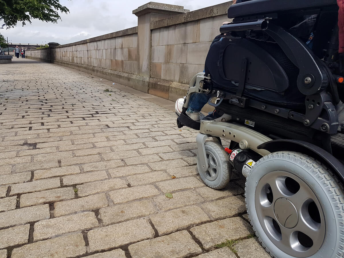 A close up of the wheels of a power wheelchair driving across cobblestone.