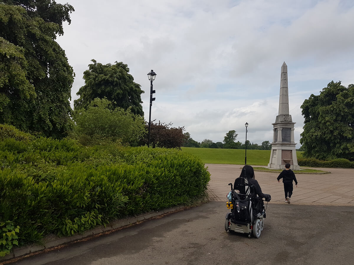 Emma driving her power wheelchair into the park towards a statue. Her nephew is walking towards the statue.