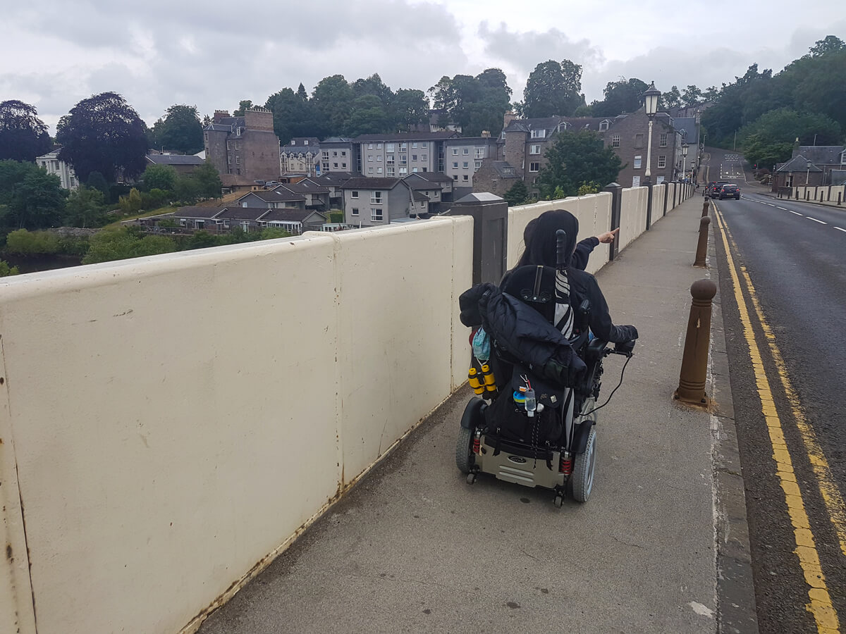 Emma driving her wheelchair across the Perth Bridge while her young nephew sits on her lap.